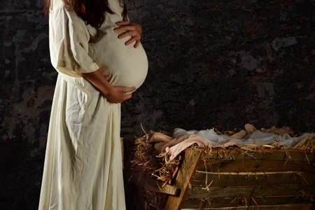 Pregnant Mary holding stomach in front of Manger