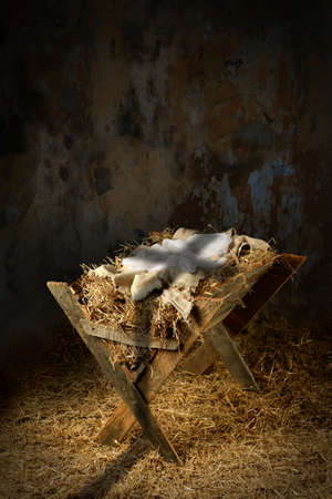 Empty manger with shadow of cross in old dirty barn