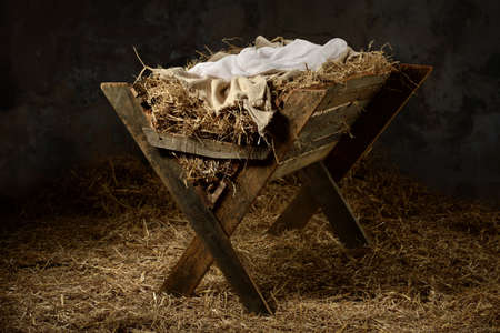 Manger with hay and swaddling clothes in old stable Stock Photo