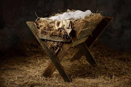 historias de la biblia: Pesebre con heno ropa y pañales en antiguo establo
