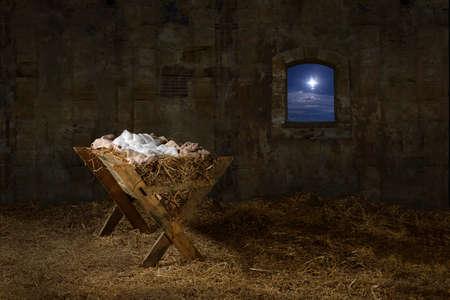 Manger in barn with window showing Christmas star Standard-Bild