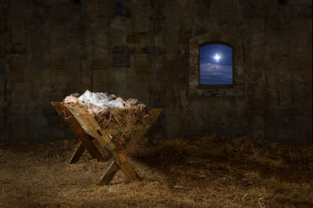 Manger in barn with window showing Christmas star Foto de archivo