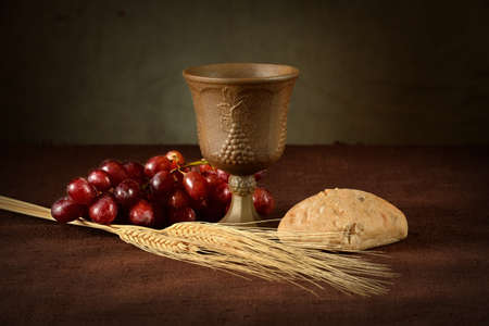 Cup of wine, red grapes, bread and wheat as symbols of Communion