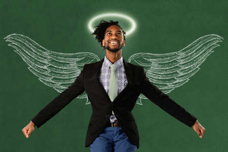 american hero: African American businessman hero with wings and halo over green surface