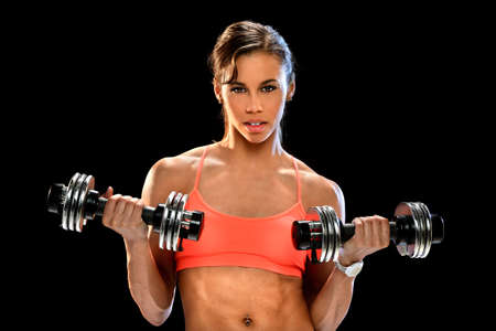 Portrait of beautiful African American woman working out with dumbells isolated over black background Banco de Imagens