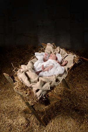 Baby Jesus on a manger inside old dark stable Stockfoto