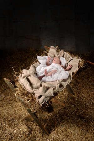 Bebé Jesús en un pesebre en el interior antiguo establo oscuro Foto de archivo - 63774219