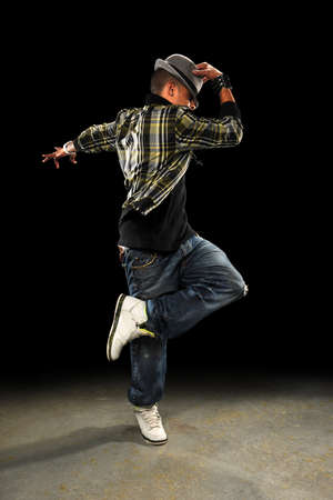 African American hop hop dancer performing over dark background photo