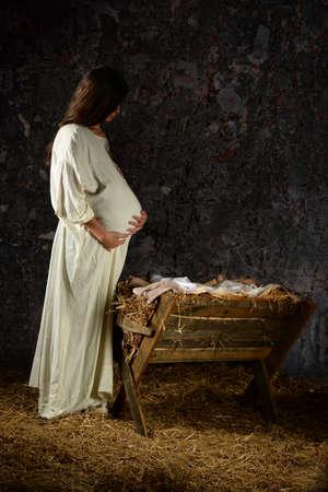 Maria zwanger overweegt in de voorkant van de kribbe Stockfoto