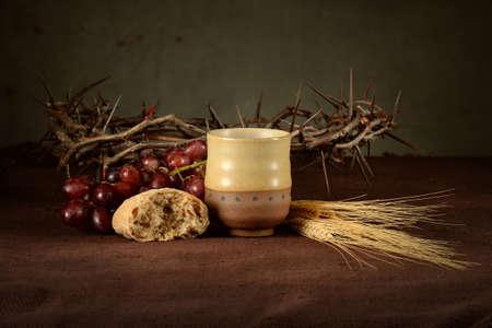 Communie concept met een beker wijn, brood, kroon van doornen, rode druiven en tarwe op tafel
