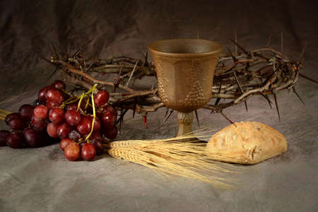 Wine cup surrounded by bread and grapes with crown of thorns in background as symbols of communion