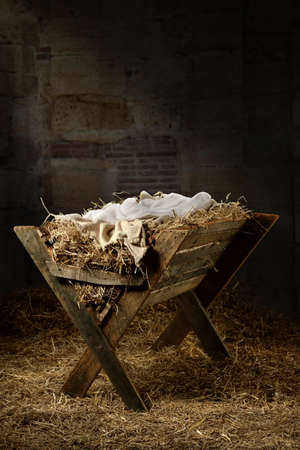 Manger filled with hay in stable with baby soft cloths on top