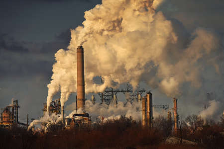 smoke stack: Thick smoke coming out of stacks at oil refinery at sunset Editorial