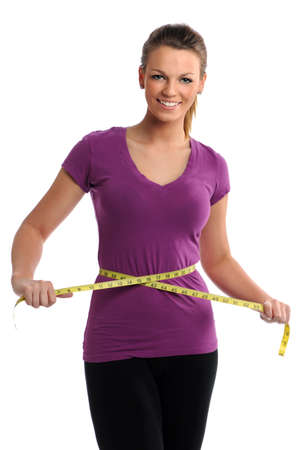 Beautiful young woman measuring waist with tape isolated over white background