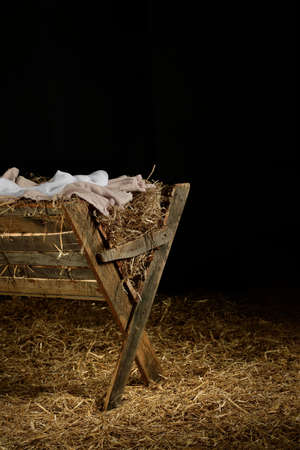 View of manger on straw covered floor over dark background Stock Photo