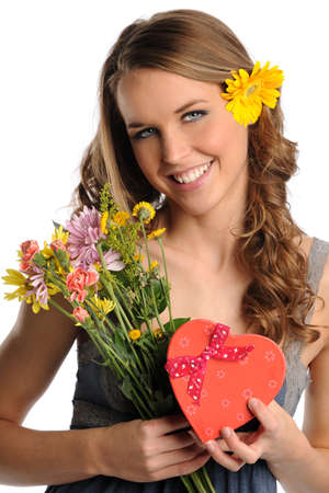 Beautiful young woman holding flowers and heart shaped gift box isolated over white background photo