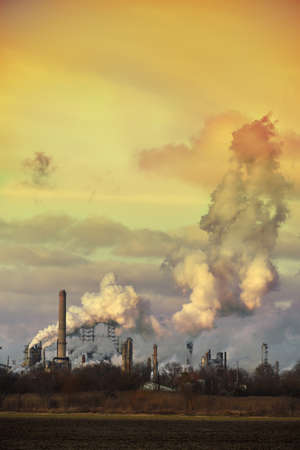 spewing: Oil refinery spewing gases from smoke stacks at sunset Editorial