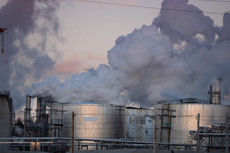 spewing: Oil refinery with storage tanks spewing gas emissions into the air Editorial