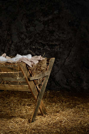 swaddling clothes: View of manger on straw covered floor in old barn Stock Photo