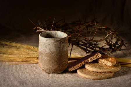 Communion elements with crown of thorns and wheat on table Imagens