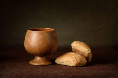Elementy komunii z kielicha wina i chleba na stole