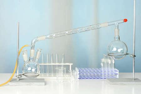 Glaswerk van het laboratorium met destillatie set op witte lijst Stockfoto