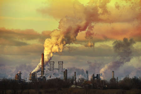 spewing: Oil refinery at sunset spewing gases from smoke stacks