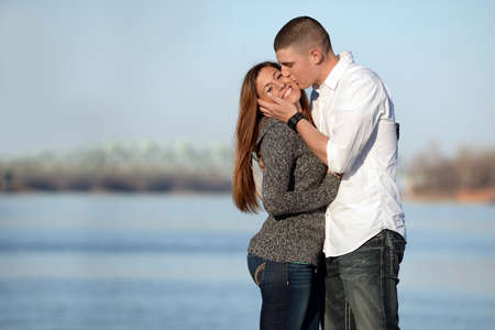 couples hug: Portrait of young couple kissing outdoors by lake Stock Photo