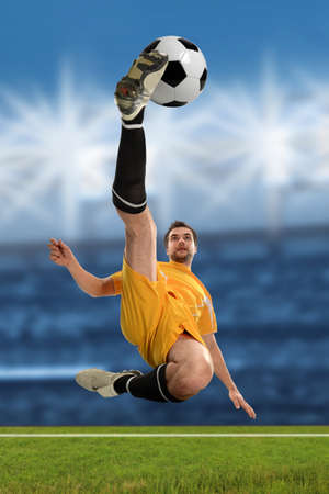 soccer player: Young soccer player performing a bicycle kick inside stadium