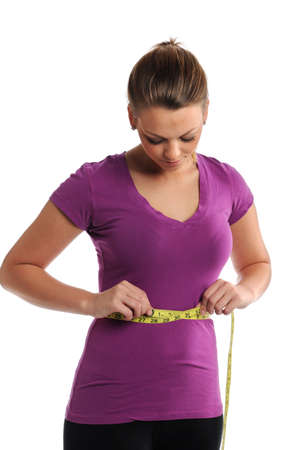 measuring waist: Young woman measuring waist isolated over white background Stock Photo