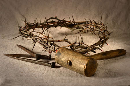Crown of thorns and nails with mallet over cloth