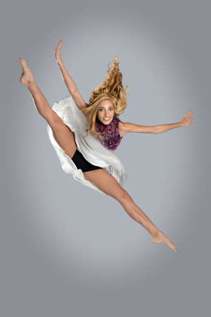 splits: Young woman jumping and doing splits over gray background