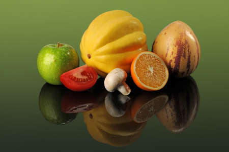 pepino: Fresh fruits and vegetables on reflective table over green background Stock Photo