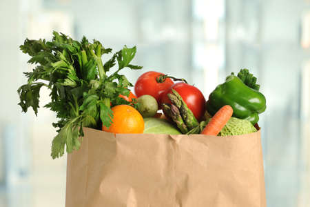 Fresh produce in paper grocery bag inside kitchen