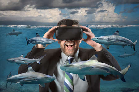 Businessman seeing sharks in the ocean using virtual reality glasses Reklamní fotografie