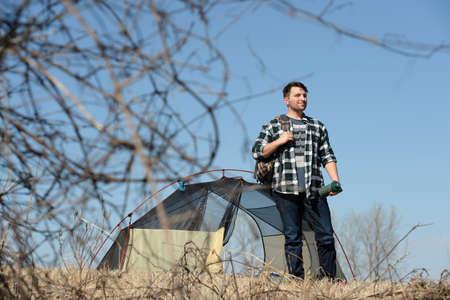 outdoorsman: Millennial outdoorsman standing near tent during sunny day