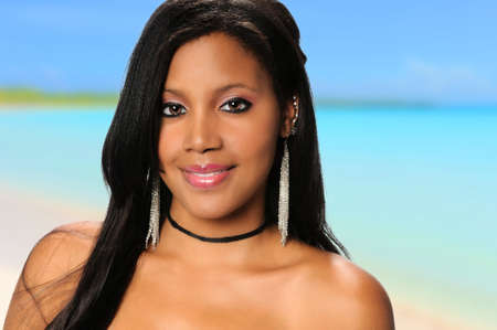 african american woman: Young African American woman smiling on the beach