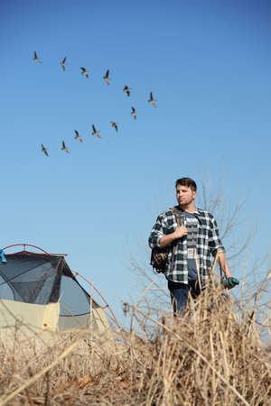 outdoorsman: Young man camping while flock of geese fly in background