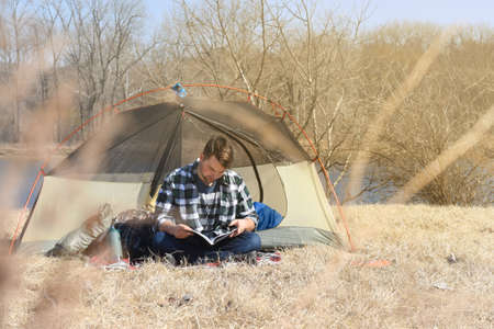 outdoorsman: Young man reading seating outside camping tent