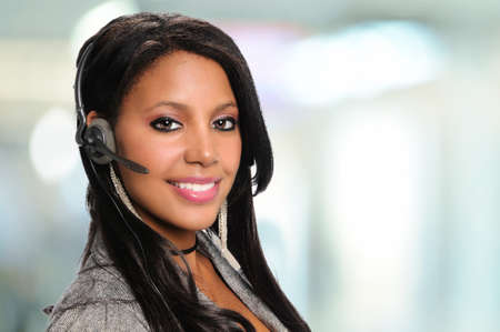 Beautiful African American businesswoman using headset inside office building