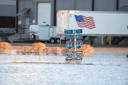 submerge: VALLEY PARK, MOUSA - JANUARY 1, 2016: Flood waters submerge highway signs in Valley Park, Missouri Editorial