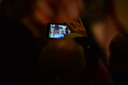 Bridgeton, MOUSA - March 08, 2016: Supporter takes video of former president Bill Clinton while speaks to crowd at political rally promoting his wife and presidential democratic candidate Hillary Clinton, at District 9 Machinists Hall in Bridgeton, a sub