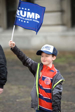 Saint Louis, MO, USA - March 11, 2016: Young Donald Trump supporter holds signs rally outside the Peabody Opera House in Downtown Saint Louis Editorial