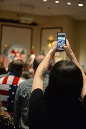 hp: Bridgeton, MOUSA - March 08, 2016: Supporter takes photo of former president Bill Clinton, at District 9 Machinists Hall in Bridgeton, outside St. Louis.