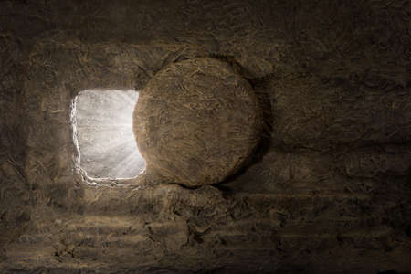 The tomb of jesus with stone rolled away and light coming from inside