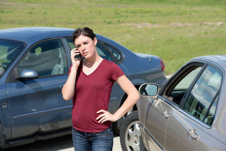 Young woman using cell phone after accident Stock Photo