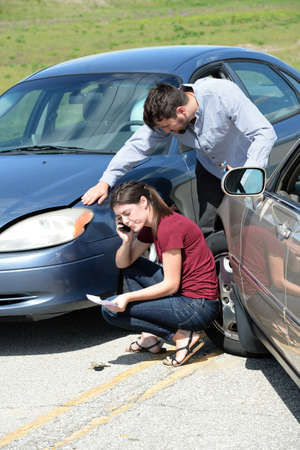 Young woman using cellphone after accident while man inspects damage