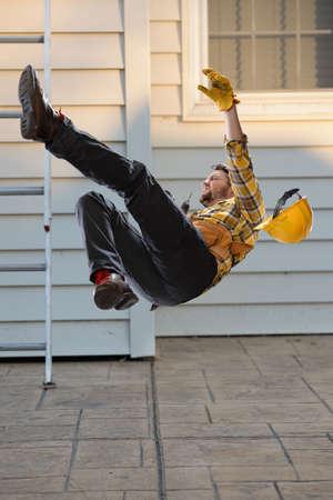 Worker falling from ladder onto floor 写真素材