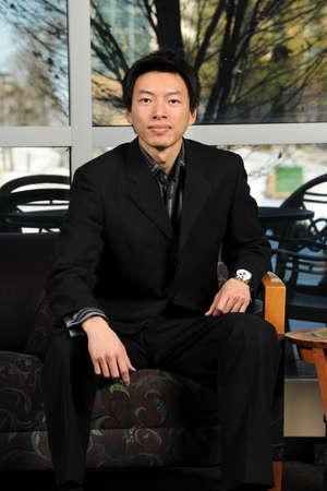 Portrait of young Asian businessman seating inside office building Reklamní fotografie