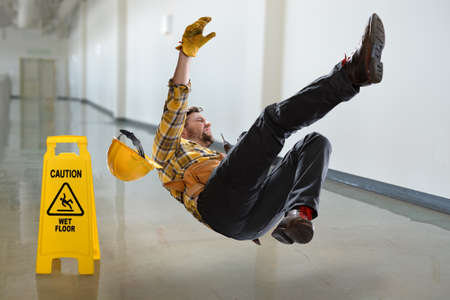 Worker falling on wet floor inside building
